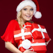 Pretty lady in Christmas cap holds a set of presents - Stock Photo