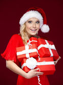 Pretty lady in Christmas cap holds a set of presents — Stock Photo