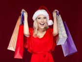 Pretty woman in Christmas cap hands packets — Stock Photo
