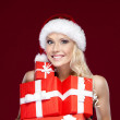 Pretty lady in Christmas cap hands a set of presents — Stock Photo