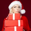 Woman in Christmas cap hands a set of presents — Stock Photo #14338337