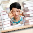 Tired young girl surrounded with books — Stock Photo