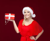 Pretty girl in Christmas cap hands a present — Stock Photo