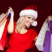 Mladá žena v vánoční čepici ruce papír pakety — Stock fotografie