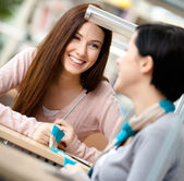 Two girls communicate sitting at the desk — Stock Photo