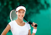Successful sportswoman with racquet at the tennis court — Stock Photo