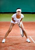 женщиной-игроком конкурирует на глины теннисный корт — Стоковое фото