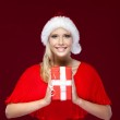 Woman in Christmas cap hands a present — Stock Photo