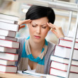Tired girl surrounded with books — Stock Photo