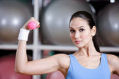 Strong young woman training with dumbbells — Stock Photo