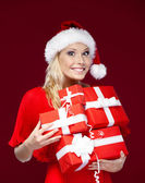 Pretty woman in Christmas cap hands a set of presents — Stock Photo
