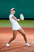 Female player plays at the clay tennis court — Stock Photo