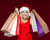 Pretty girl in Christmas cap hands packets — Stock Photo