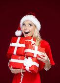 Frau in christmas mütze hält eine reihe von geschenken — Stockfoto