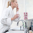 Woman washes face with lotion — Stock Photo