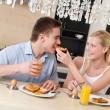 Woman feeds his husband with breakfast in the kitchen — Stock Photo #18373337