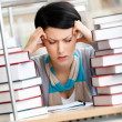 Tired young woman surrounded with books — Stock Photo #18373489
