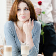 Woman at the coffee house and man with rose behind her - Foto Stock