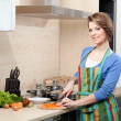 Pretty woman in striped apron cooks — Stock Photo