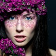 Close up of blue-eyed girl with flowers — Stock Photo