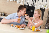 Woman feeds his husband with breakfast in the kitchen — Stock Photo