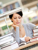 Interested woman reads at the library — Stock Photo