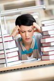 Tired young woman surrounded with books — Stock Photo