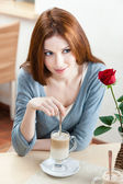 Woman with scarlet rose at the cafe — Stock Photo