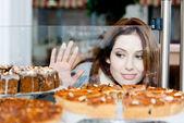 Mujer bonita en bufanda mirando el escaparate de la panadería — Foto de Stock