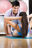 Athletic woman does situps with coach — Stock Photo