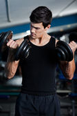 Handsome muscular man uses his dumbbells — Stock Photo