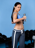 Sportive woman exercises with dumbbells — Stock Photo