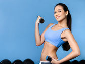 Woman works out with dumbbells — Stock Photo