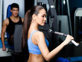 Athletic young woman works out on fitness gym equipment — Stock Photo