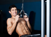 Athletic man works out on training gym equipment — Stock Photo