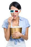 Viewer watching 3D movie with bowl of popcorn — Stock Photo