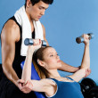 Coach helps woman to exercise with weights - Stock Photo
