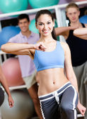 Sexy female coach trains with her group — Stock Photo