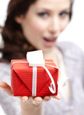 Young woman shows a present — Stock Photo