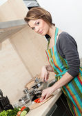 Femme en tablier rayé cuit les légumes — Photo
