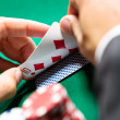 Gambler checking his poker cards — Stock Photo #18976043