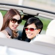 Two happy girls sitting in the car glance back — Stock Photo
