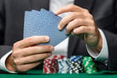 Gambler playing poker cards with poker chips on the table — Stock Photo