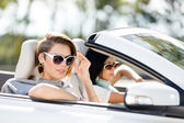 Close up view of girls in sunglasses in the automobile — Stock Photo