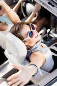 Girl in the car with her hands up — Stock Photo