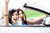 Two happy friends ride the cabriolet — Stock Photo