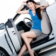 Pretty woman sits in the white car with door opened - Stock Photo