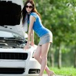 Woman repairing the broken car on the street — Stock Photo