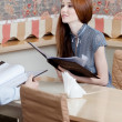 Woman holds the menu to make an order - Stock Photo