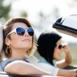 Close up of girls in sunglasses in the white car - Stock Photo
